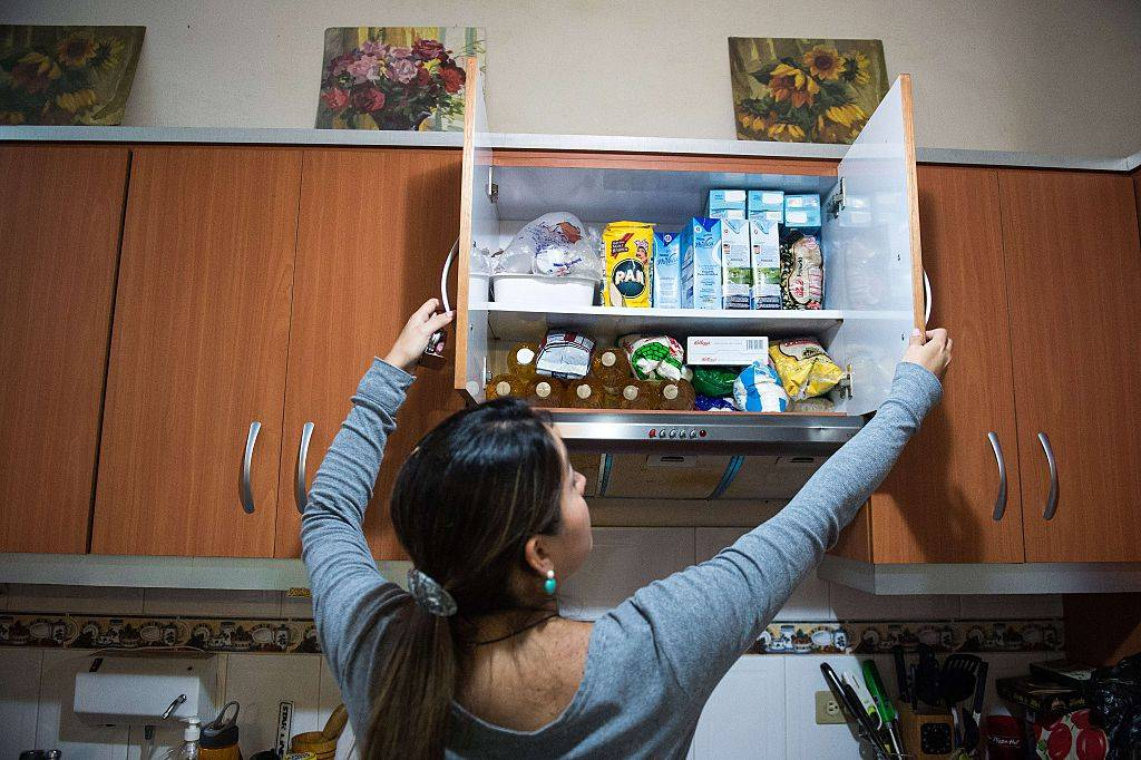 A woman opens up her kitchen cabinet.