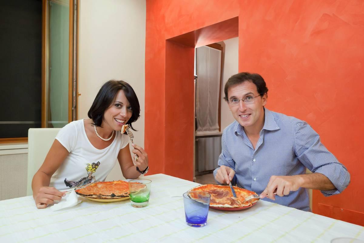 A couple eats pizza happily.