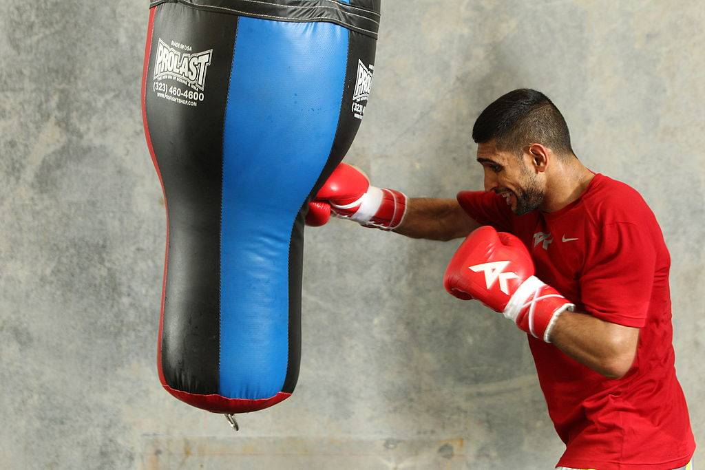 A boxer punches a heavy bag.