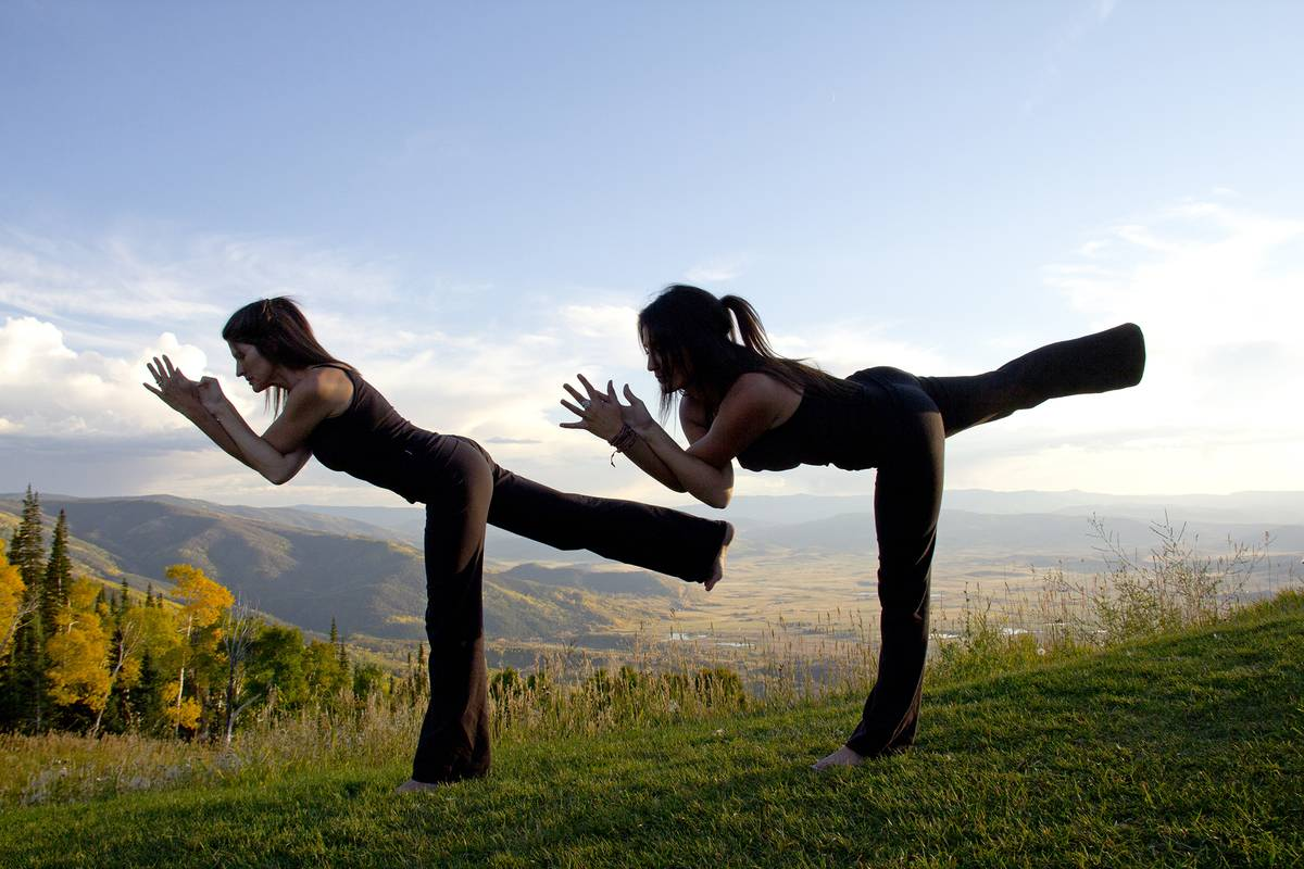 Two yoga instructors practice together in nature.