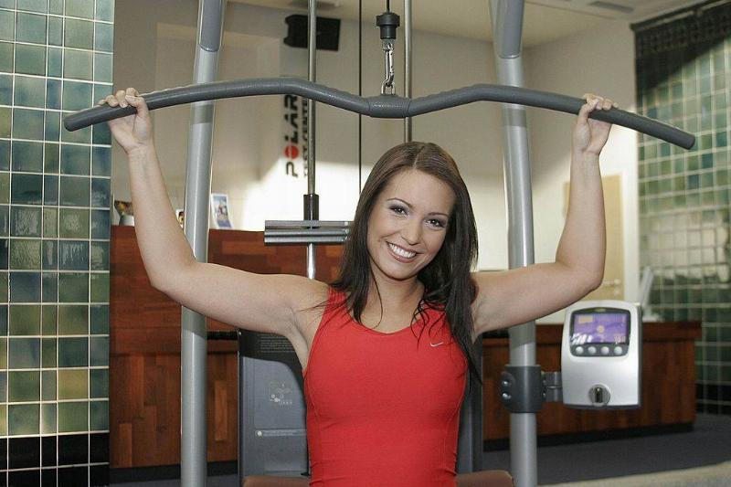 A woman uses a lateral pulldown machine.
