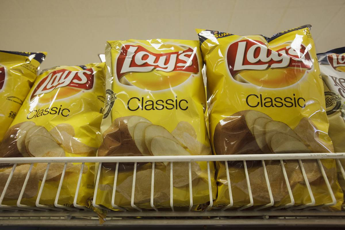 Bags of Lays chips are stocked on a shelf at a supermarket.