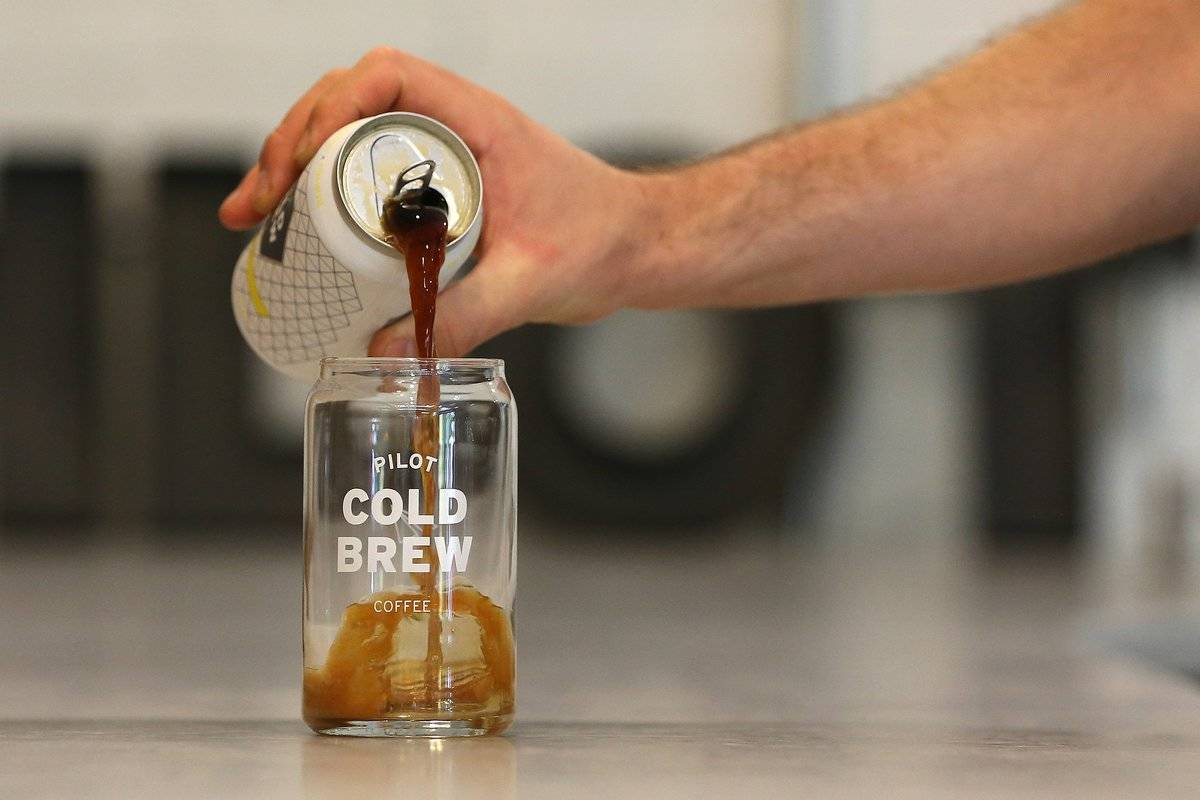 A man pours canned cold brew coffee into a glass.