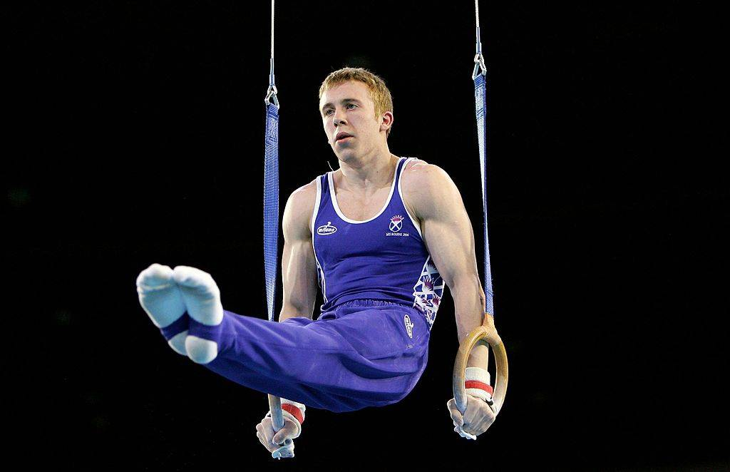 A gymnast holds himself up with gym rings.
