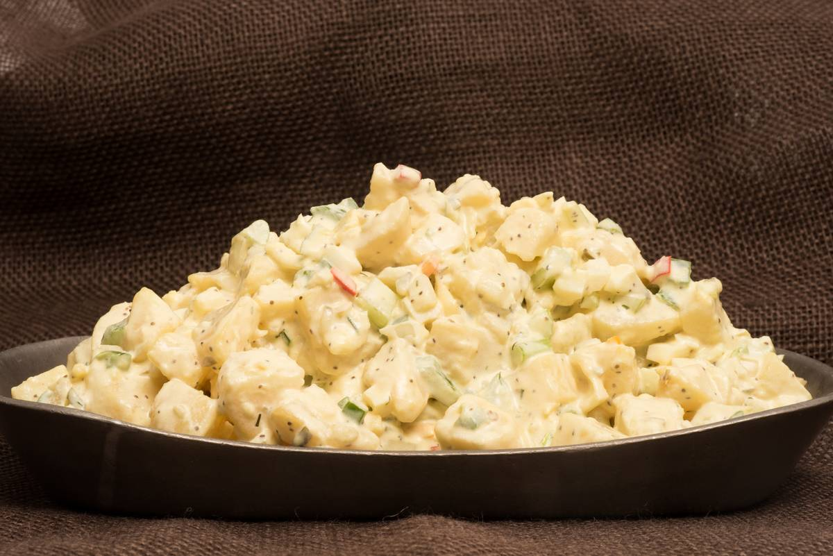 A bowl of potato salad is piled high.