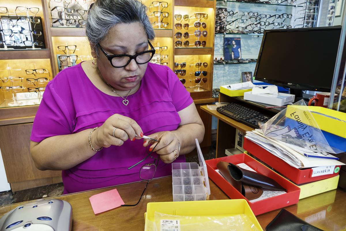A woman repairs eye glasses.