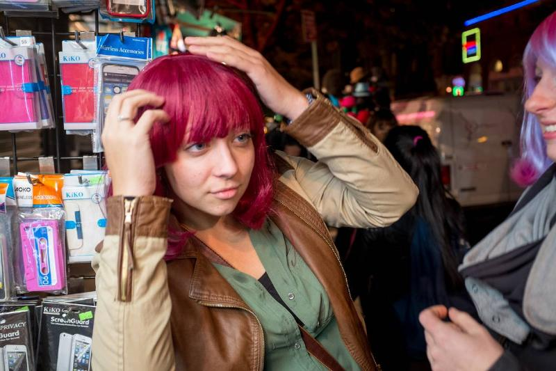 A young woman smiles as she tries on a brightly colored wig.