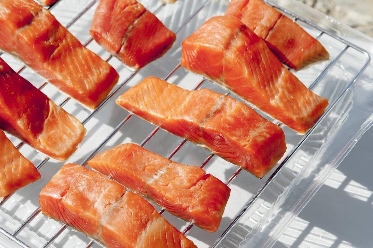 Raw salmon filets sit on a grill rack.