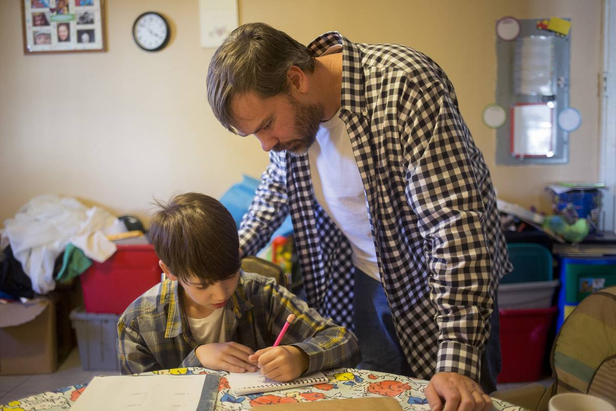 A father helps his son with ADHD with his homework.