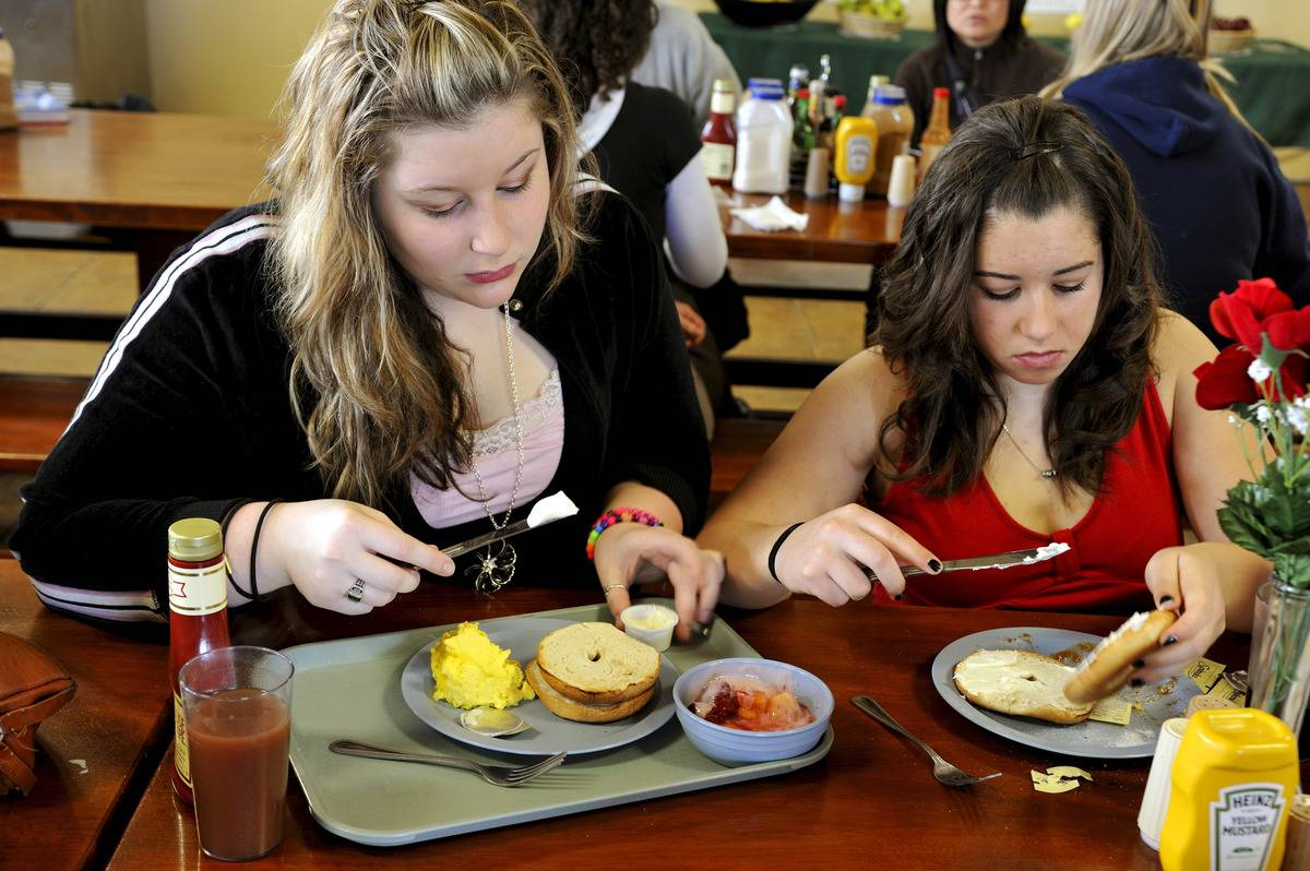 Two young women eat bagels with cream cheese for breakfast.