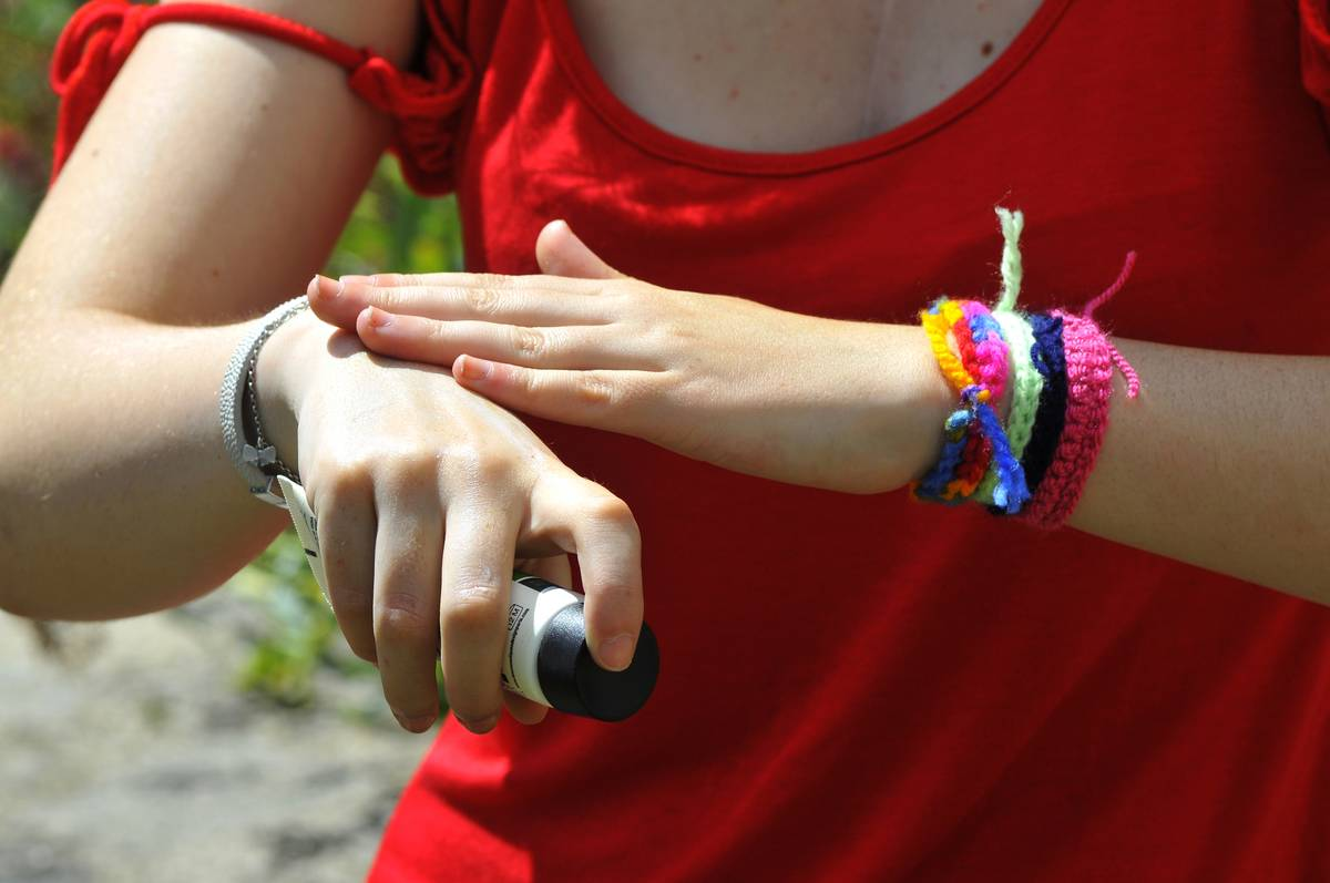 A woman rubs cream on her wrist.
