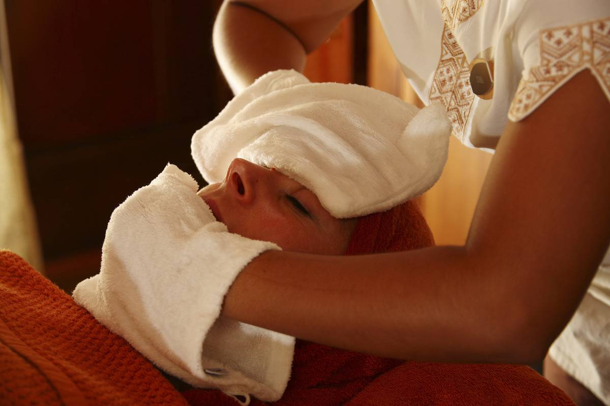 A woman presses warm towels on another woman's face.