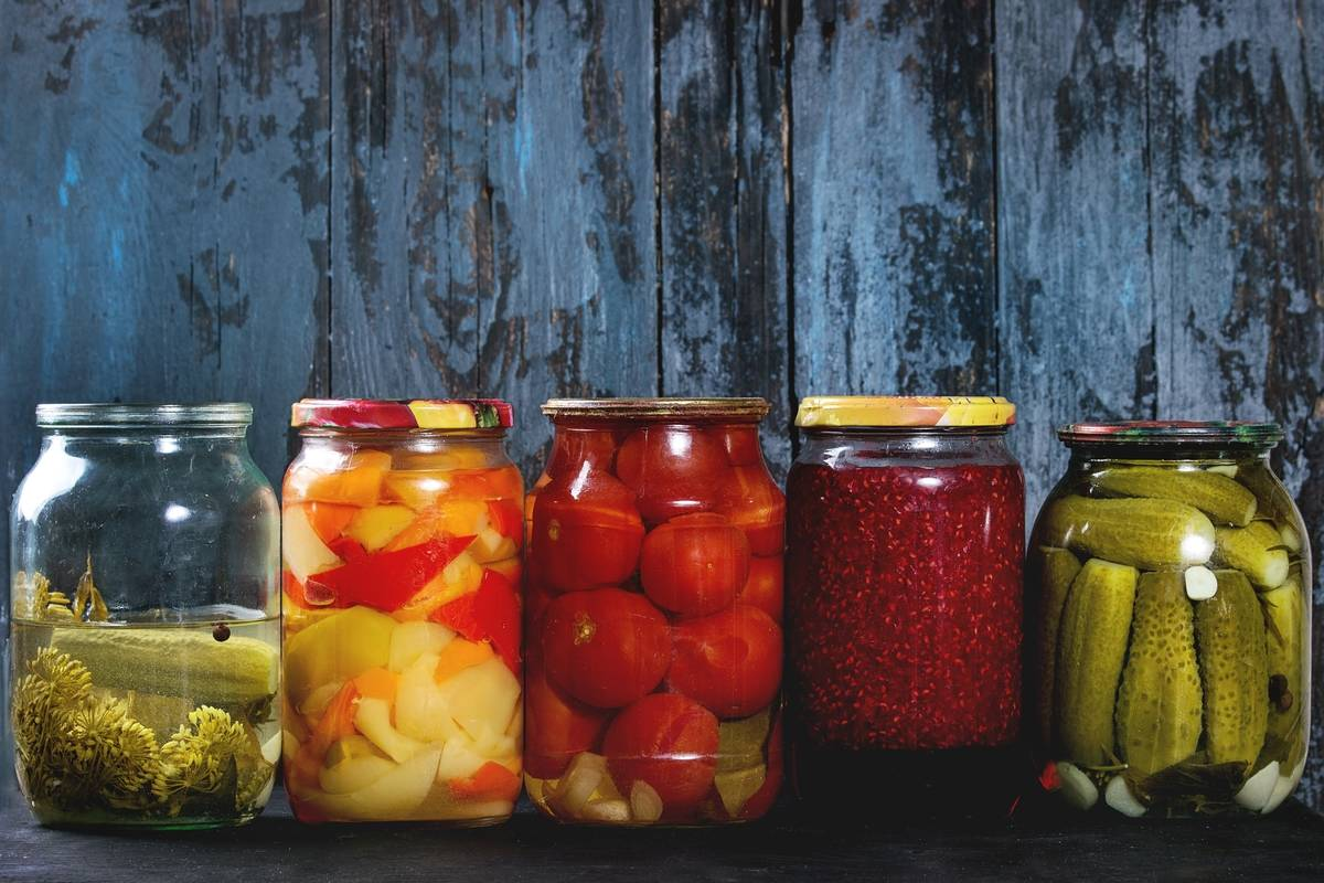 Variety glass jars of homemade pickled or fermented vegetables and jams sit in row