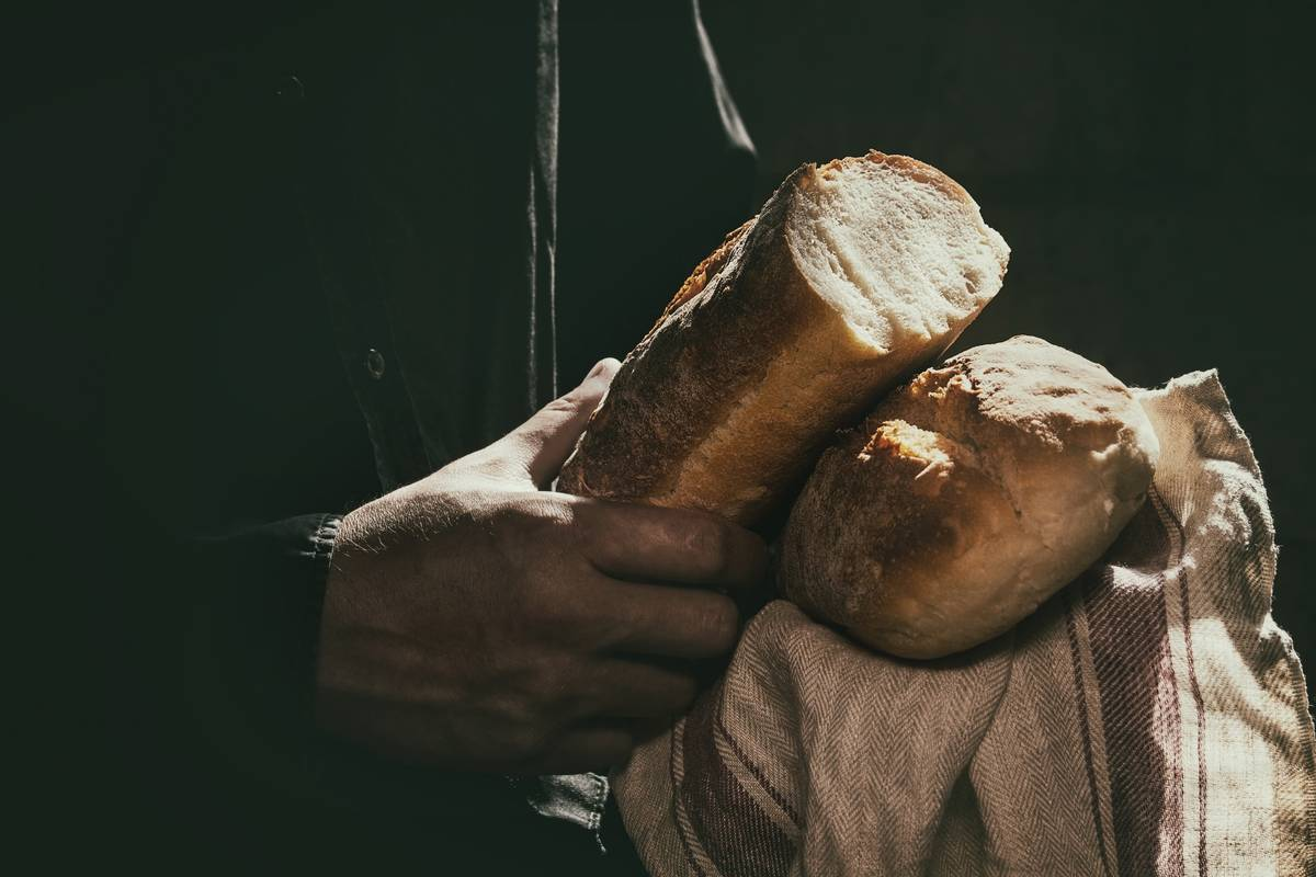 A man creates open a loaf of white bread.