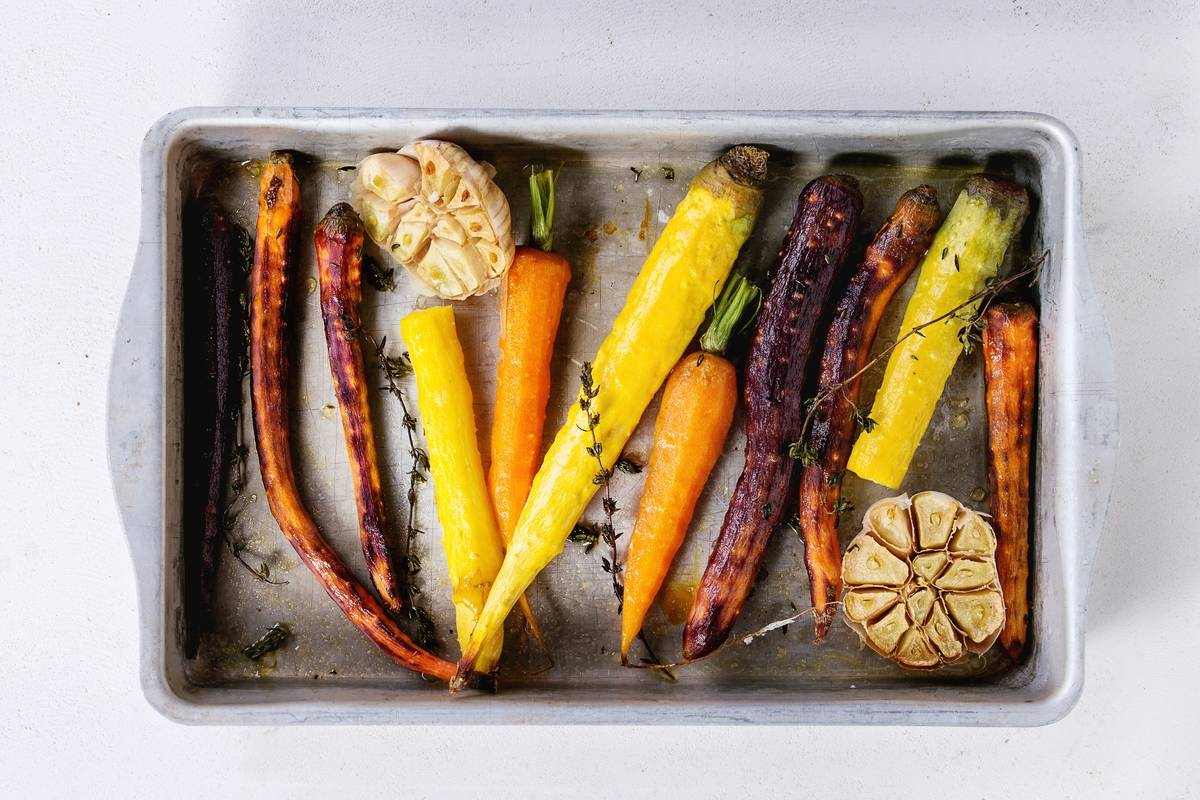 Baked whole colorful carrots with garlic and thyme sit in vintage aluminum tray.