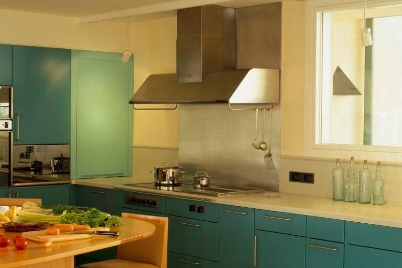 A kitchen has a large range hood.
