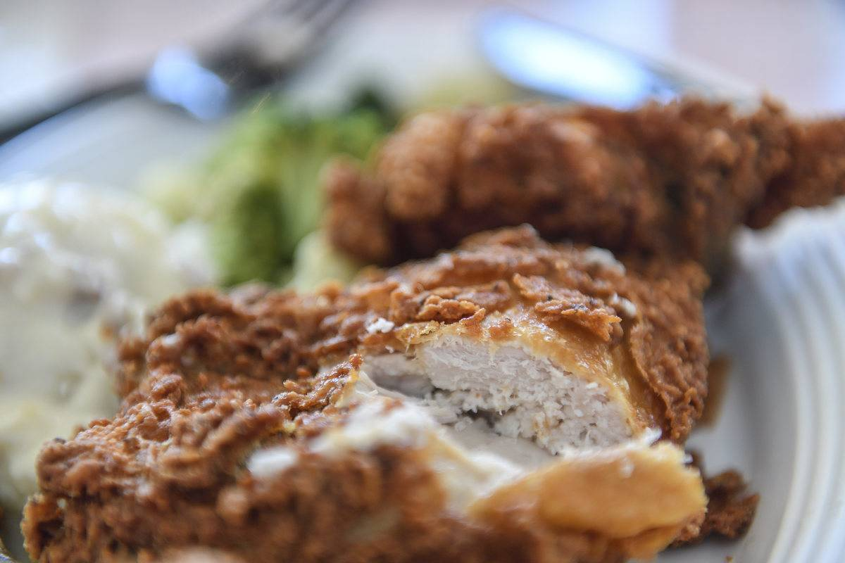 A close-up shows cut fried chicken thighs.