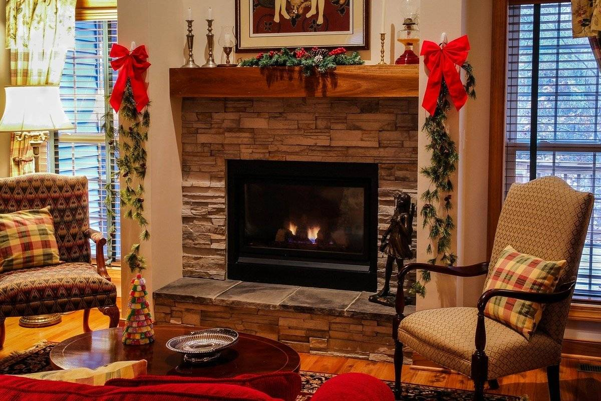 A fireplace burns in a room decorated for Christmas.
