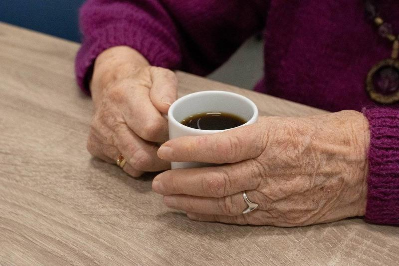 An elderly woman holds a mug of coffee.