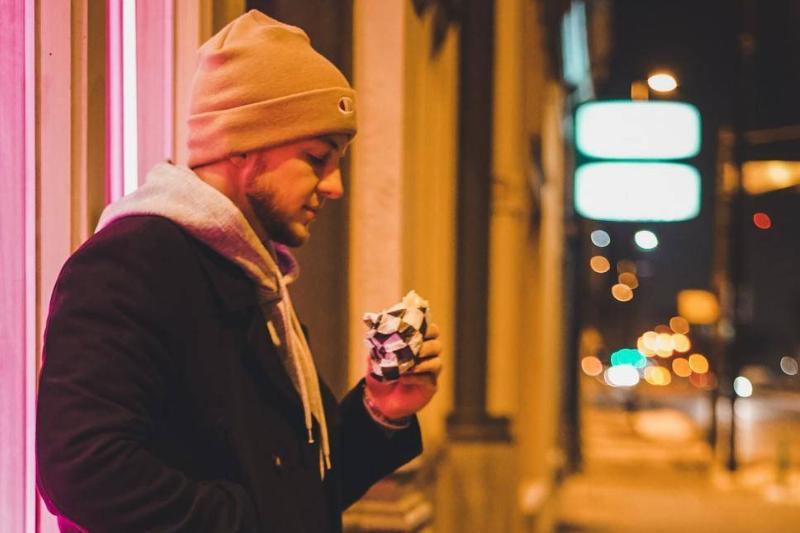 A man eats outside late at night.