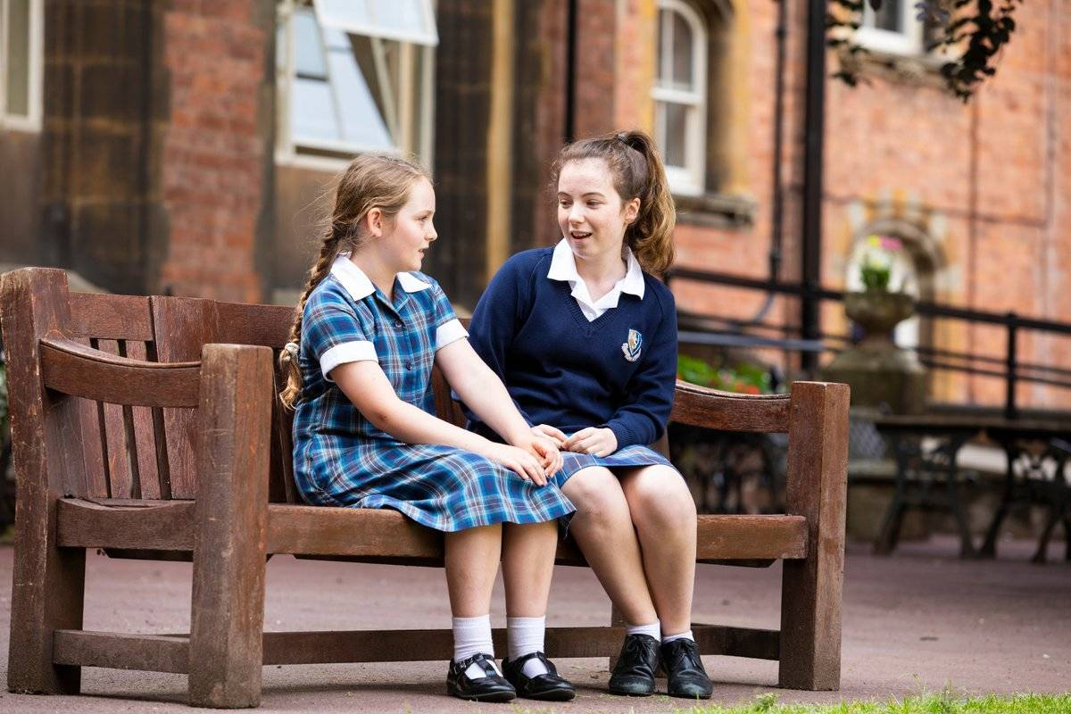 Two school girls talk on a bench.