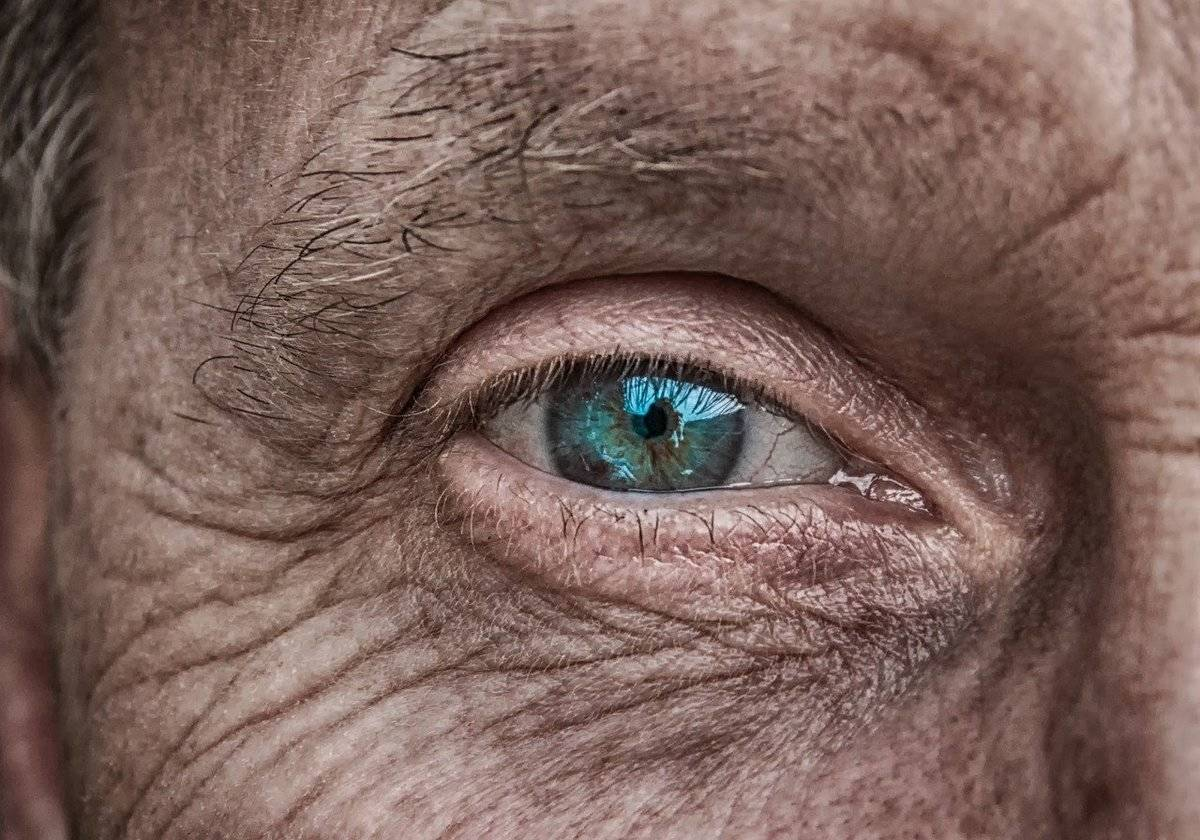 A close-up shows wrinkles around a man's eye.
