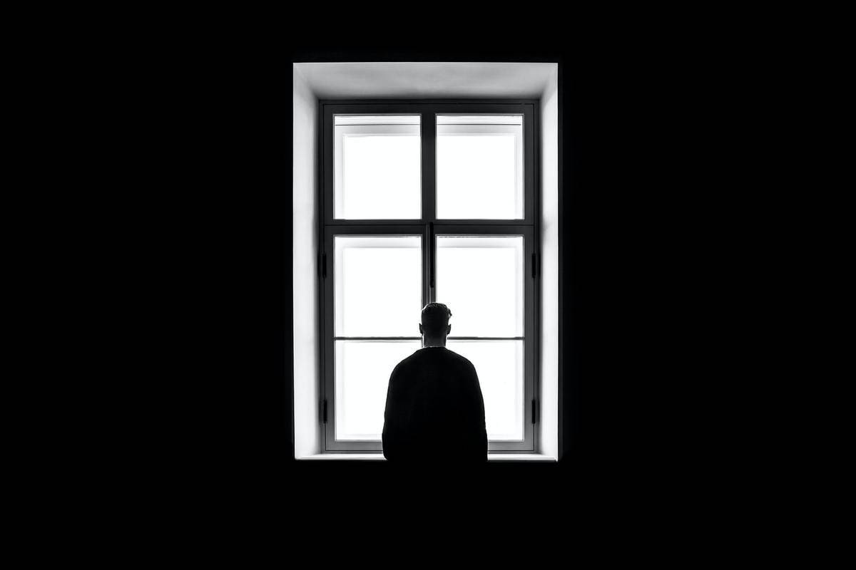 A man stands in front of a window in the dark.