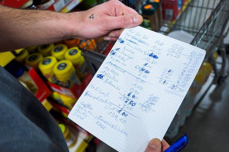 A man checks his grocery list while shopping.