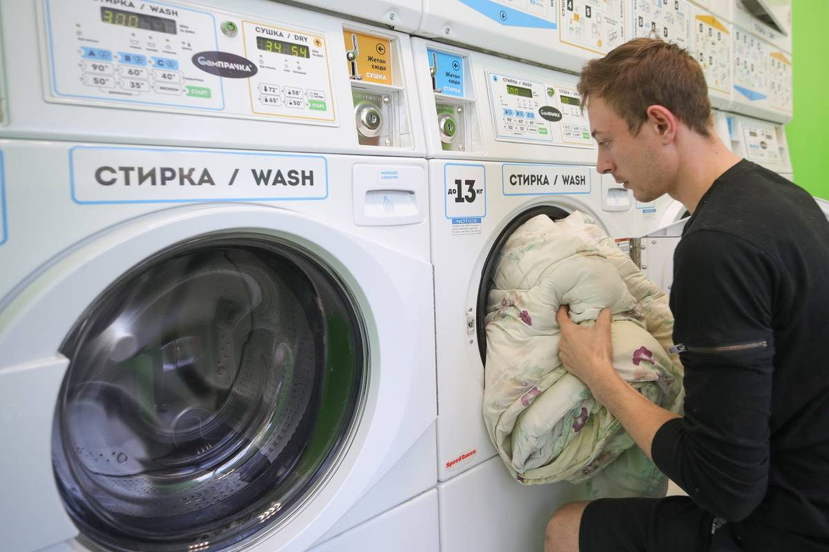 A man pushes laundry into a washing machine.