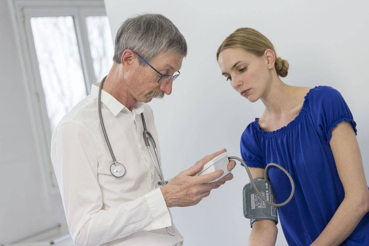 A doctor measures a patient's blood pressure.
