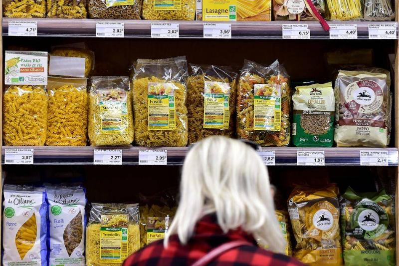 A woman stands in front of a pantry filled with organic pastas.