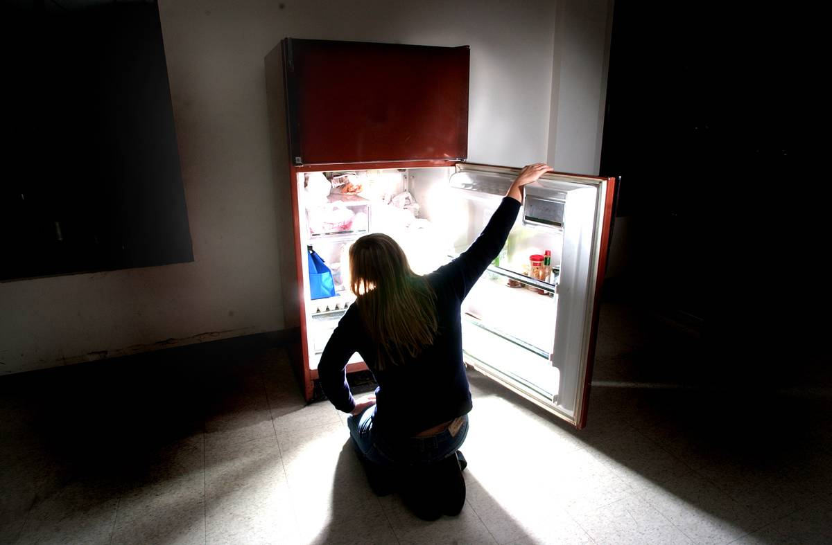 A woman opens her fridge late at night.