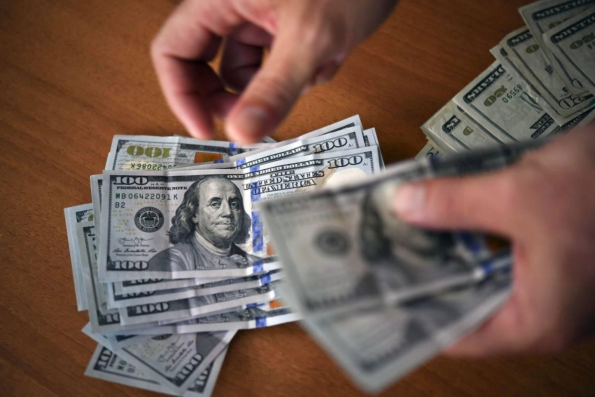 A man counts US $100 bills.
