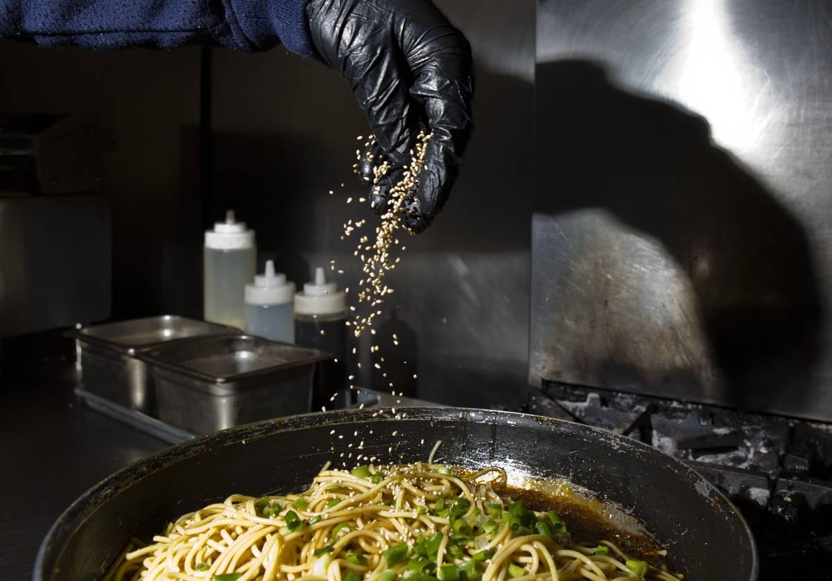A chef sprinkles sesame seeds onto Teriyaki Noodles.
