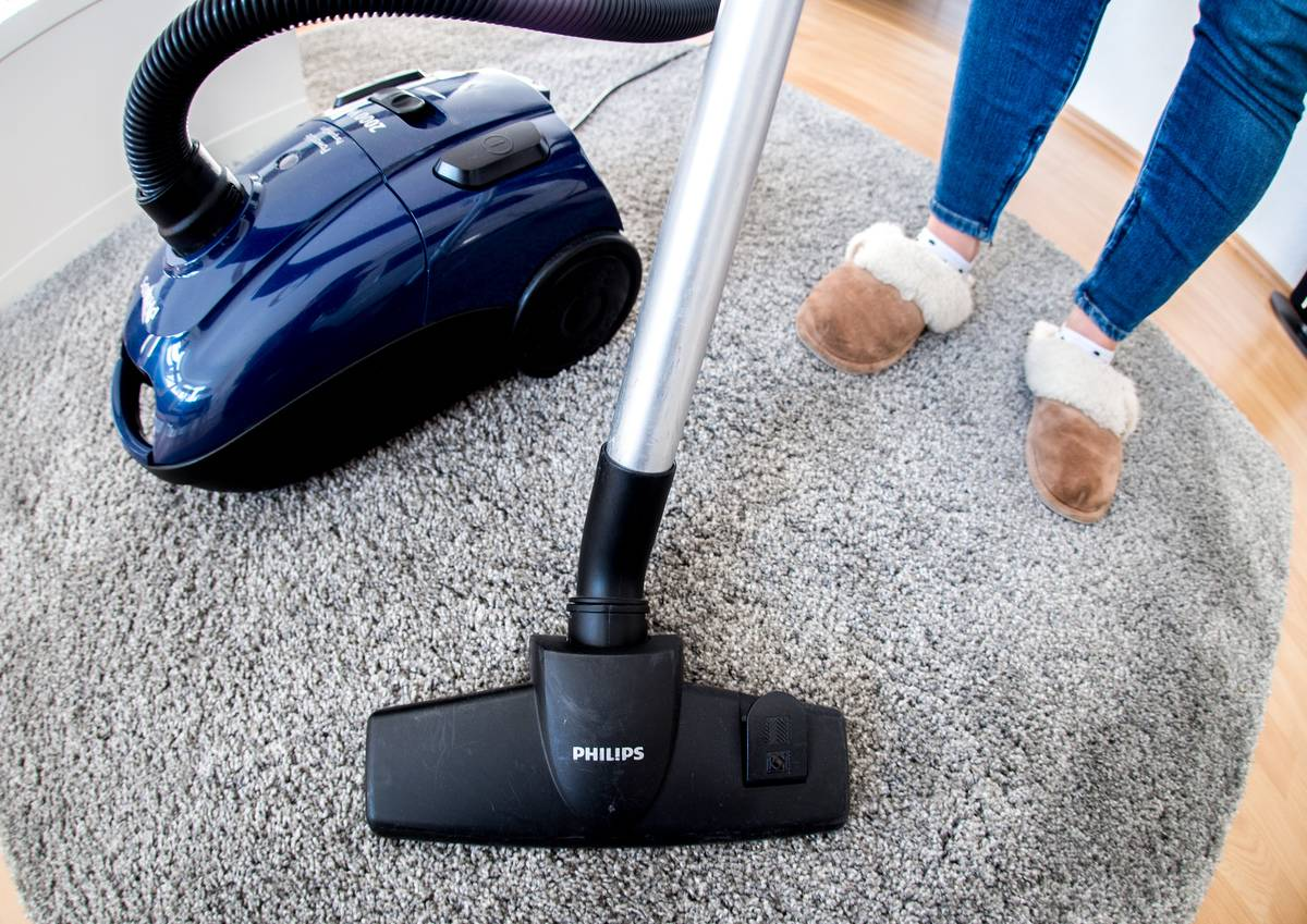 A woman vacuums her grey rug.