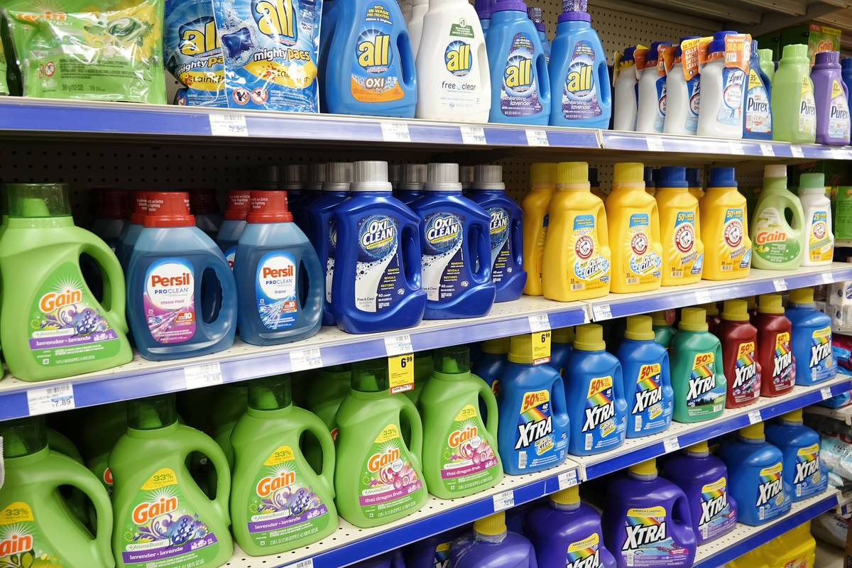 Several brands of laundry detergent sit on shelves in a CVS Pharmacy.