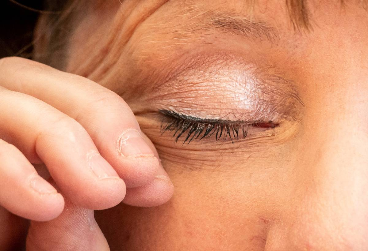 A close-up shows a woman rubbing her eye.