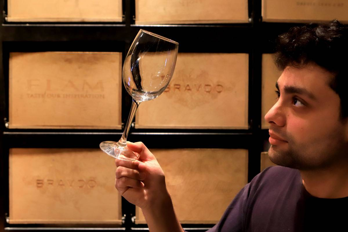 A man holds up an empty wine glass.