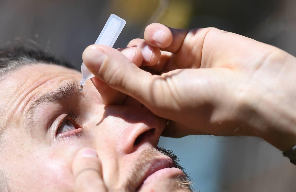 A man puts eye drops into his eye.