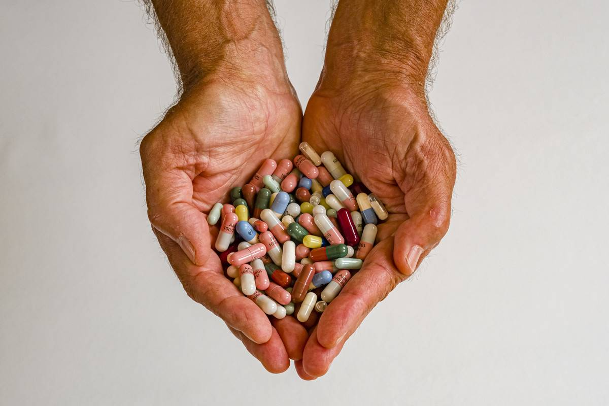 A man's cupped hands hold supplements.