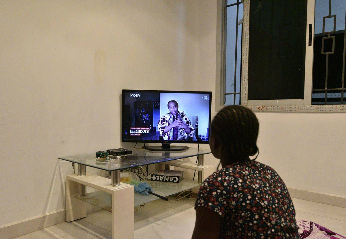 A woman watches an artist perform on her TV.