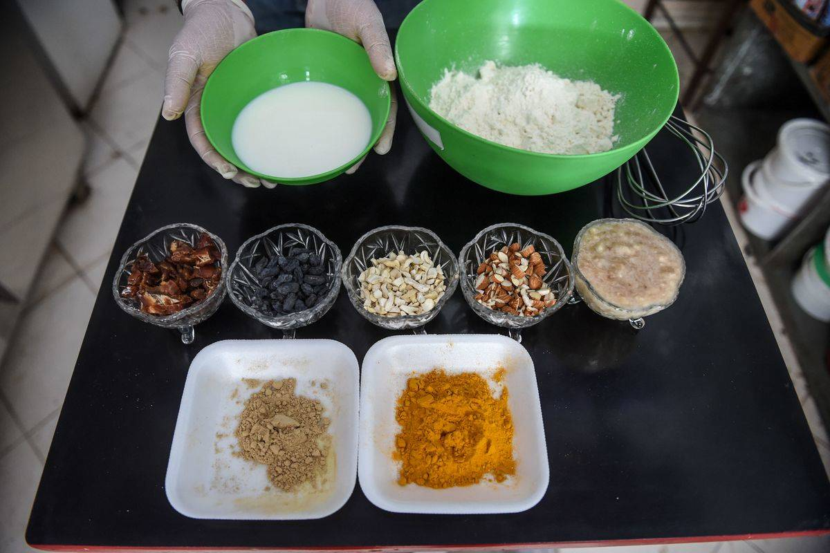 An Indian cake baker lays out ingredients in separate bowls.