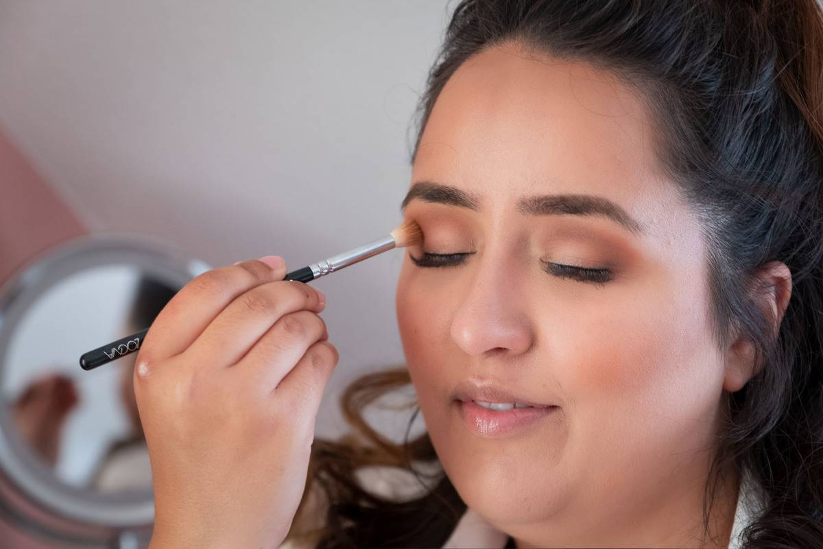 A woman applies eye shadow.