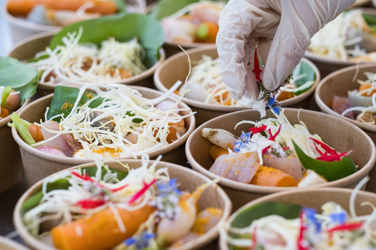 A chef adds some flowers to meals sorted into to-go containers.