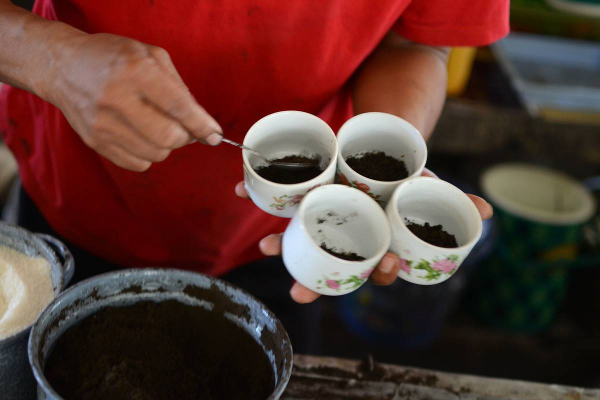 A man dishes coffee grounds from cups.