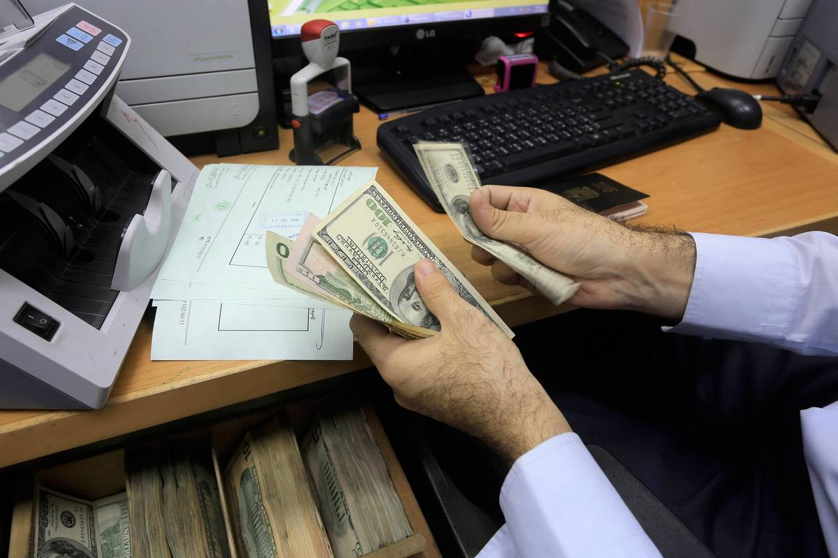 A man counts dollar bills at his desk.