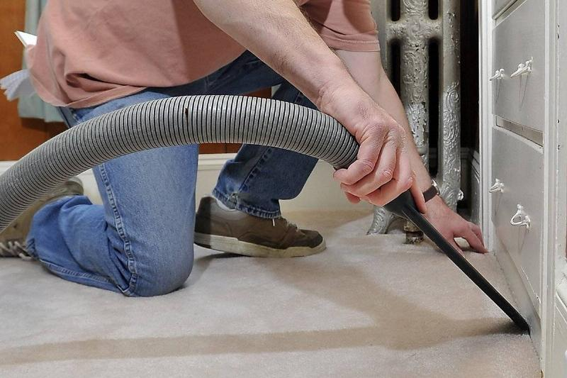 A man steam cleans a corner of a carpet.