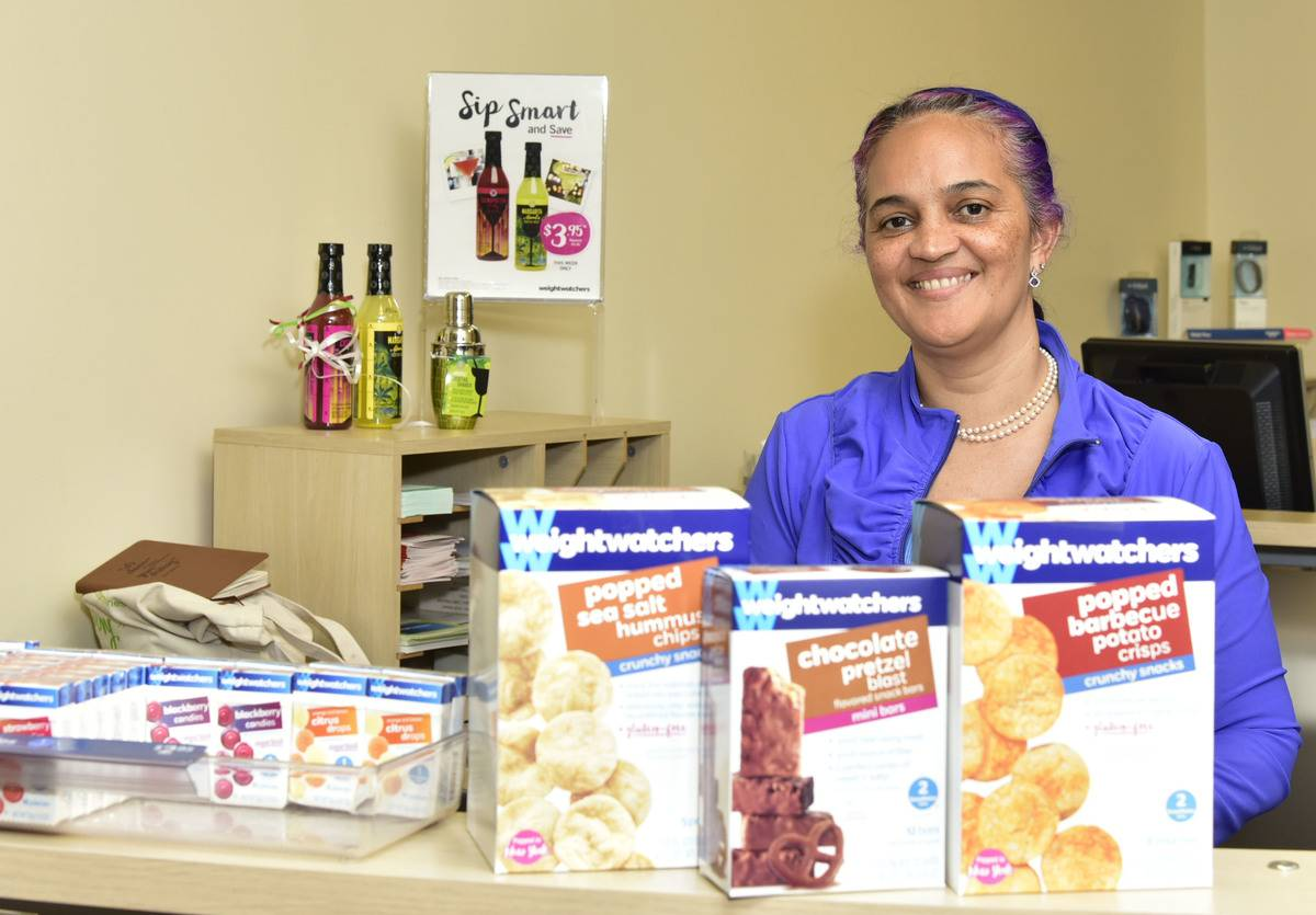 An employee stands behind Weight Watchers snacks at a store location.