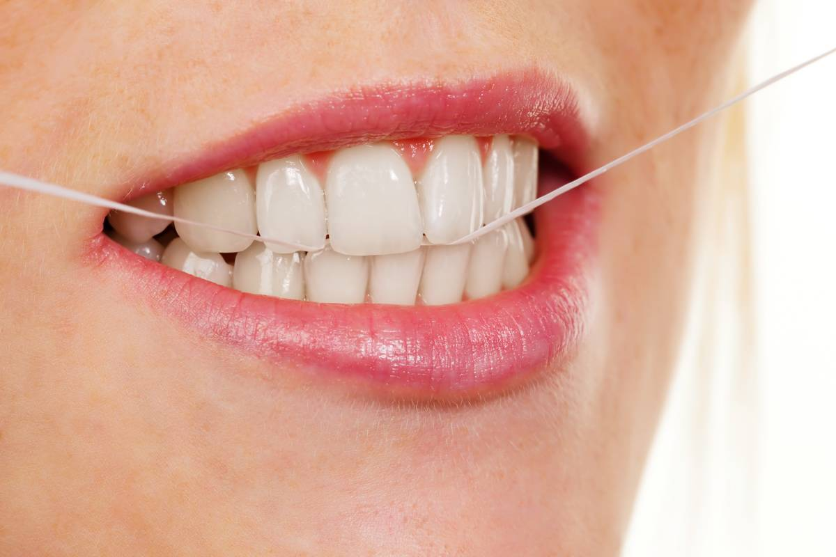 A woman holds floss to take care of her teeth.