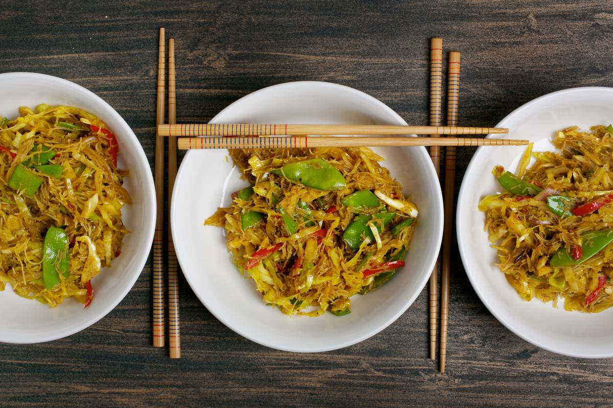 Stir-fried noodle dishes from Singapore are photographed.
